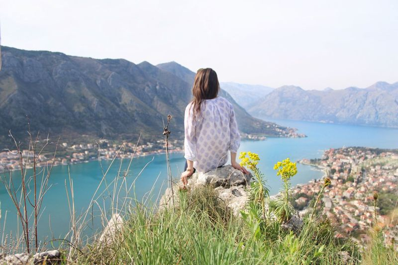 Rear view of woman sitting on rock against lake and mountains
