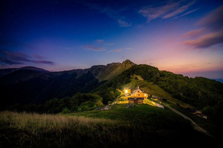 Illuminated houses on mountains against sky at dusk