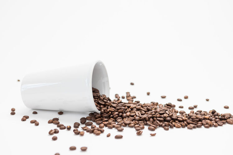 Overturned White Coffee cup with Coffee Beans Inside on a White Background White Background Studio Shot Roasted Coffee Bean Indoors  Still Life Copy Space Food And Drink Coffee - Drink Coffee Large Group Of Objects Close-up Food Freshness No People Brown Refreshment Cup Spilling Cut Out Abundance Caffeine