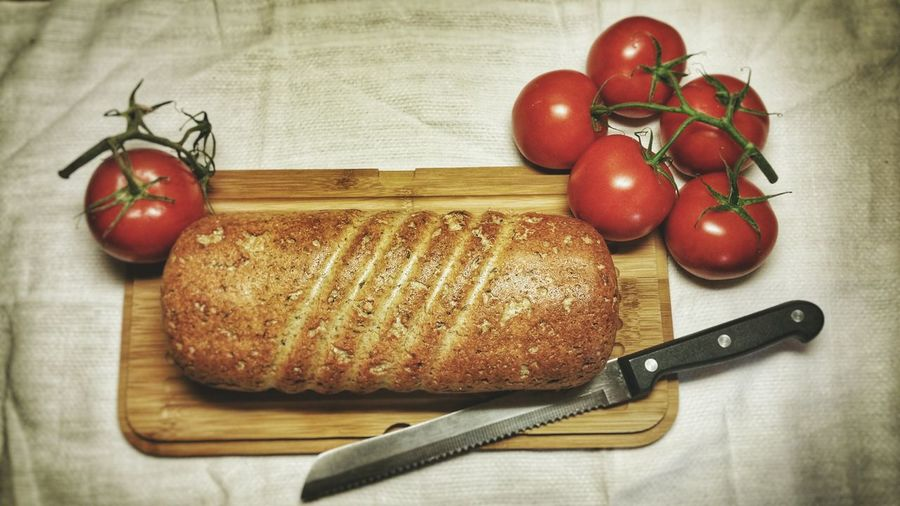 High Angle View Of Bread And Tomatoes With Knife On Cutting Board