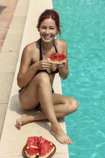 Young woman eating watermelon by the pool Young Adult Sitting One Person Full Length Beautiful Woman Young Women Outdoors Watermelon Eating Pool Poolside Plate Vacation Bikini Red Hair Smiling Swimming Pool Food And Drink Leisure Activity Holding Lifestyles Food Front View Water Happiness Real People Portrait Hairstyle Mallorca Mediterranean
