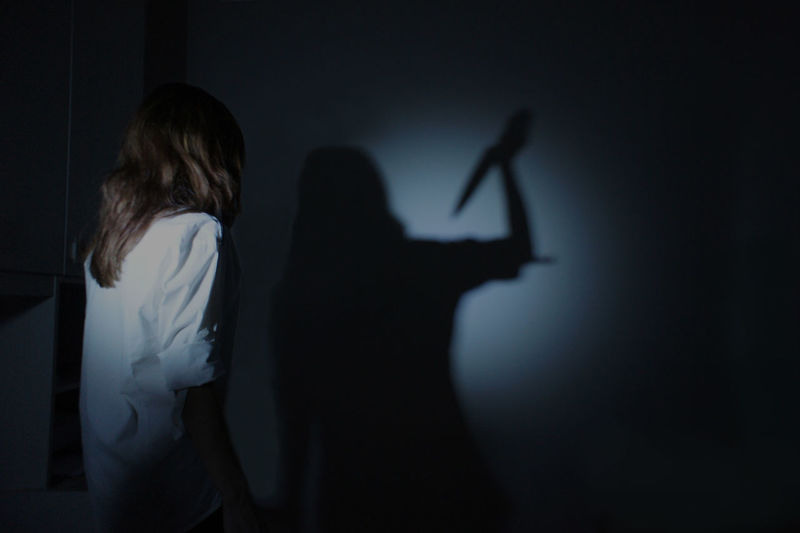 Woman looking at shadow with knife standing on wall