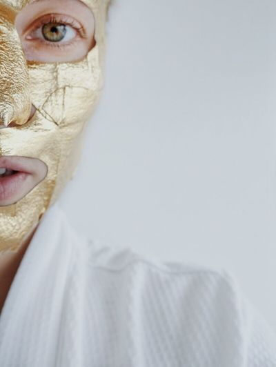 Cropped portrait of woman with golden facial mask over white background
