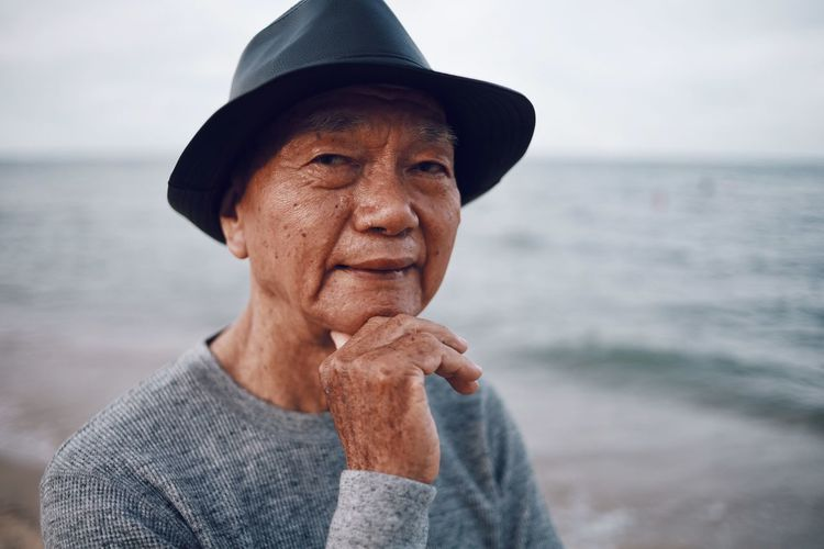 Portrait of senior man wearing hat standing at beach against sky during sunset