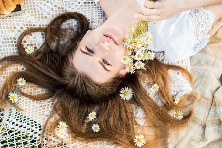 High angle portrait of woman lying on bed while holding flowers