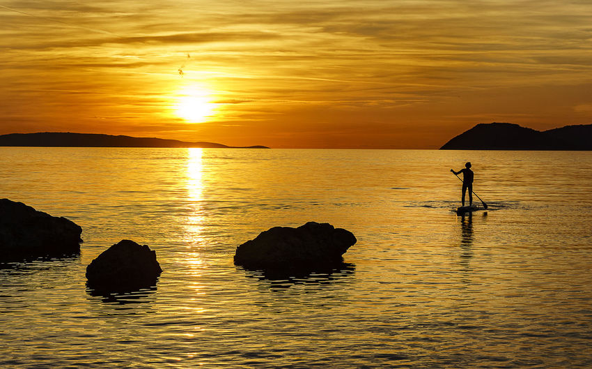 Paddling Into the Sunset Sunset Water Sky Beauty In Nature Orange Color Silhouette Waterfront Tranquil Scene Scenics - Nature Tranquility Sea One Person Reflection Idyllic Rock Lifestyles Outdoors Real People Nature Cloud - Sky Stand Up Paddling Sun Paddling Ocean Adriatic Sea