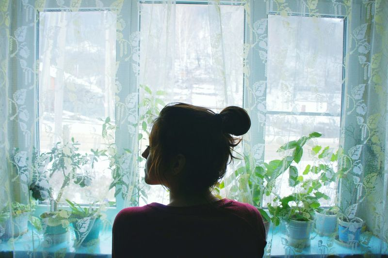 Rear view of woman at home against window
