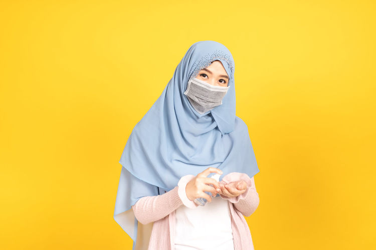 Portrait of a woman against yellow background