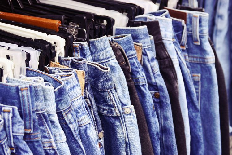 close up Many jeans hanging on rack Jeans Large Group Of Objects Clothing No People Denim Choice Hanging Textile Fashion In A Row Collection Variation For Sale Casual Clothing Group Abundance Still Life Blue Group Of Objects