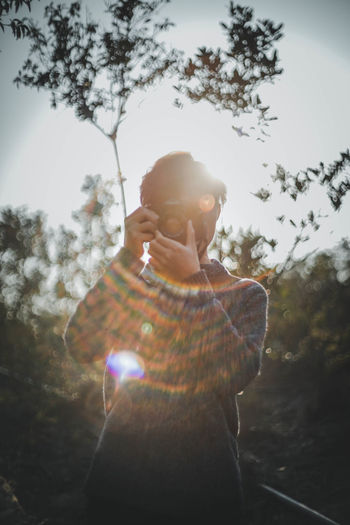 One Person Tree Real People Lens Flare Sunlight Leisure Activity Waist Up Nature Lifestyles Plant Day Standing Young Men Outdoors Technology Sky Sunbeam Casual Clothing Young Adult Bright My Best Photo
