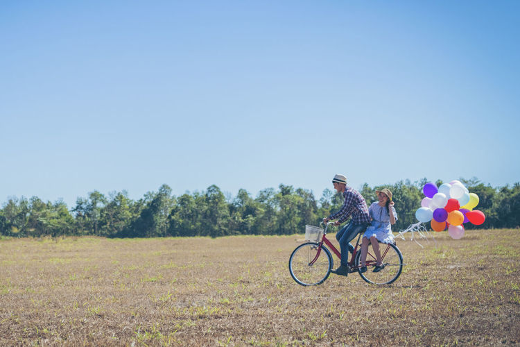 Man riding bicycle on field against clear blue sky