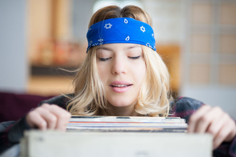 Beautiful blond woman searching records at store