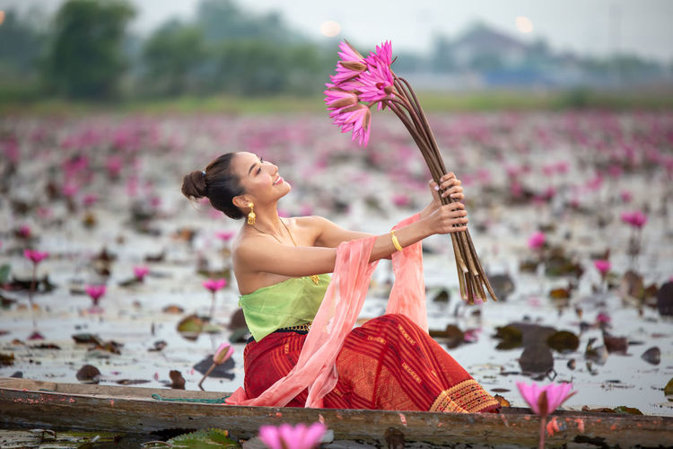 Young woman holding water lilies sitting in boat on lake
