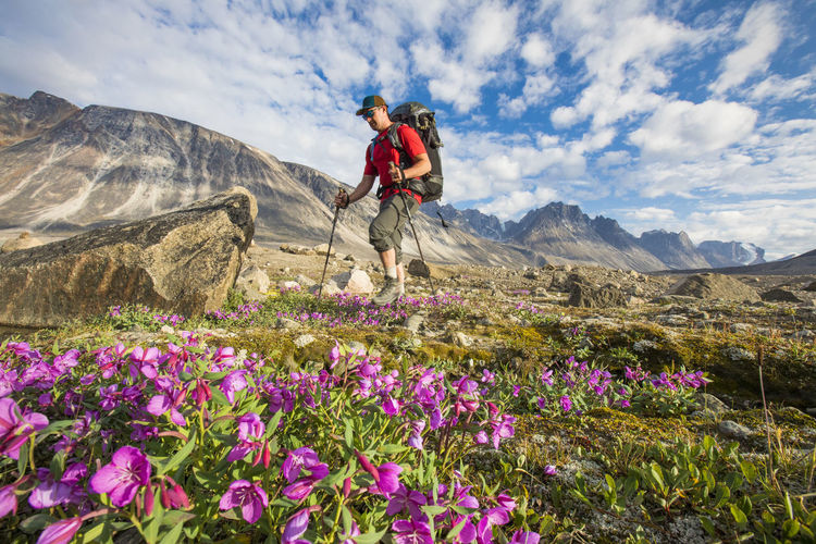 Man riding flowers on mountain against sky