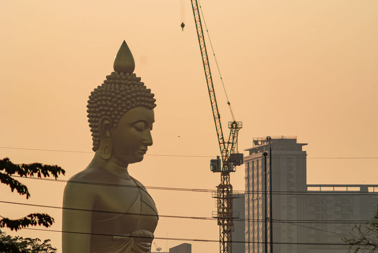 Statue of temple against building against clear sky