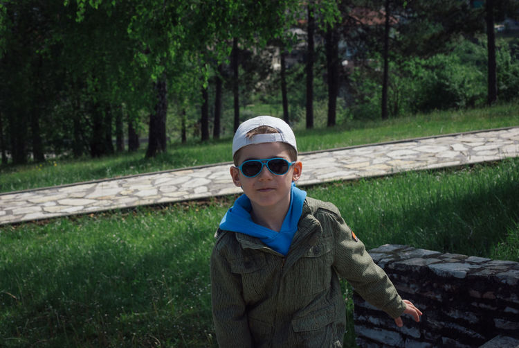 Portrait Of Boy In Sunglasses Standing On Grassy Field At Park
