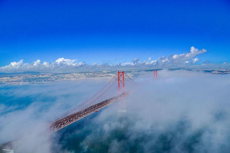 Aerial view of bridge over water against blue sky. 25th april bridge, lisbon, portugal