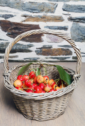 Cherries in a rustic wicker basket on a wooden work surface with a stone wall background Basket Cherries Delicious Food Freshness Fruit Healthy Eating Healthy Food Leaves No People Raw Food Red Ripe Rustic Stone Wall Whicker Wood