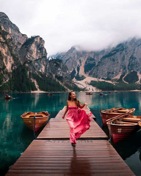 Woman on boat in lake against mountains