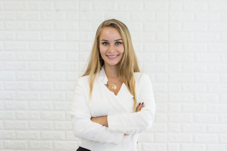 Portrait Of Young Businesswoman Smiling While Standing Against White Brick Wall
