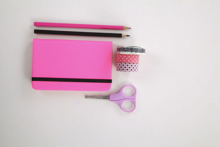 High angle view of pink paper over white background