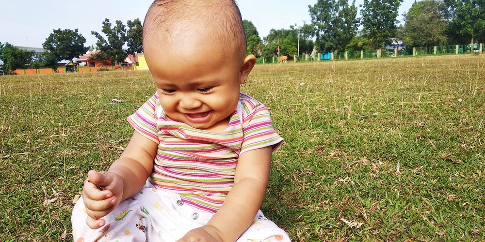 Close-Up Of Cute Smiling Baby Girl Sitting On Grassy Field