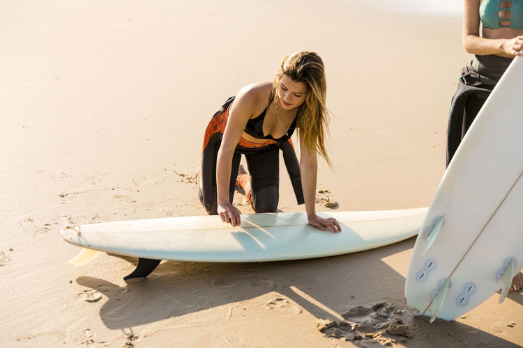 Female friends with surfboards at beach
