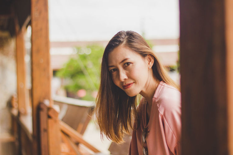 Woman sitting on the balcony Beautiful Woman Beauty Brown Hair Casual Clothing Contemplation Hair Hairstyle Headshot Leisure Activity Lifestyles Long Hair Looking Looking At Camera One Person Outdoors Portrait Real People Standing Women Young Adult Young Women