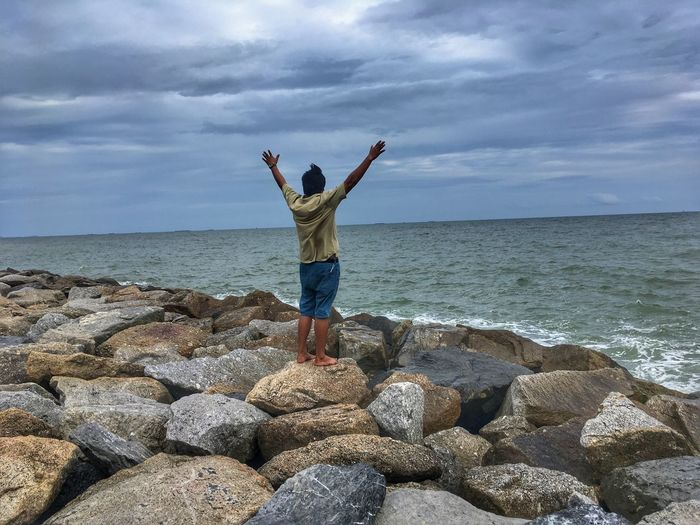 Man with arms raised standing on rock at beach against sky