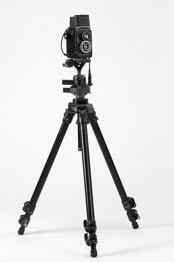 twin lenses antique camera mounting on the tripod Camera Photography Multimedia Tripod Photograph Lens Equipment Photographic Theme Photographing Black Nobody White Background Twin Lense Medium Format Camera Old Antique Ancient Photography Themes Technology No People Camera - Photographic Equipment Studio Shot Photographic Equipment Indoors  Still Life Arts Culture And Entertainment Cable Cable Release Photo Shoot Filming Activity
