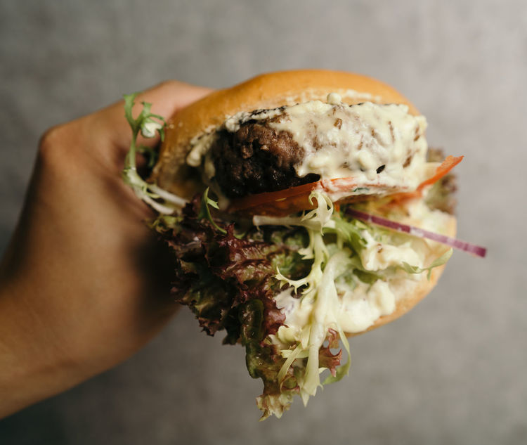 Pressing a burger Human Hand Hand Human Body Part Food Holding One Person Freshness Food And Drink Indoors  Close-up Ready-to-eat Real People Unrecognizable Person Body Part Lifestyles Focus On Foreground Meat Sandwich Healthy Eating Finger Human Limb 2018 In One Photograph