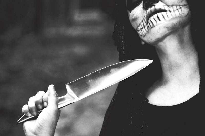 Close-up of woman in halloween make-up holding knife
