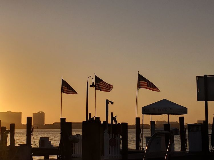 3 US flags blowing in the wind Us Flags Sunset Silhouette Sky Skyscraper No People