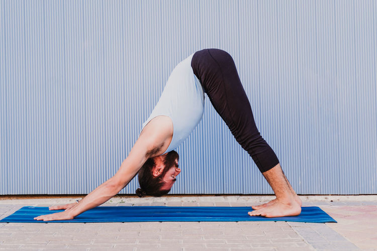 Full length of young woman doing yoga on exercise mat against wall