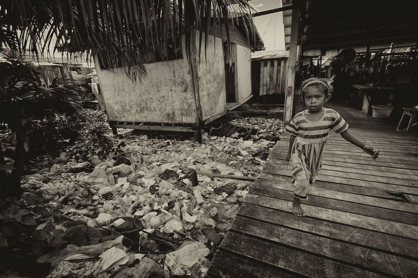 Young girl at heavily polluted floating village in Semporna, Sabah. Architecture Back Yard Backyard Bajaulaut Bench Borneo Building Exterior Built Structure Day Footpath Gypsea Mabul Monochrome Narrow Outdoors Polluted Sabah Sea Sephia Photo Sepia Solitude Streetphotography Sulu Tone Tranquility