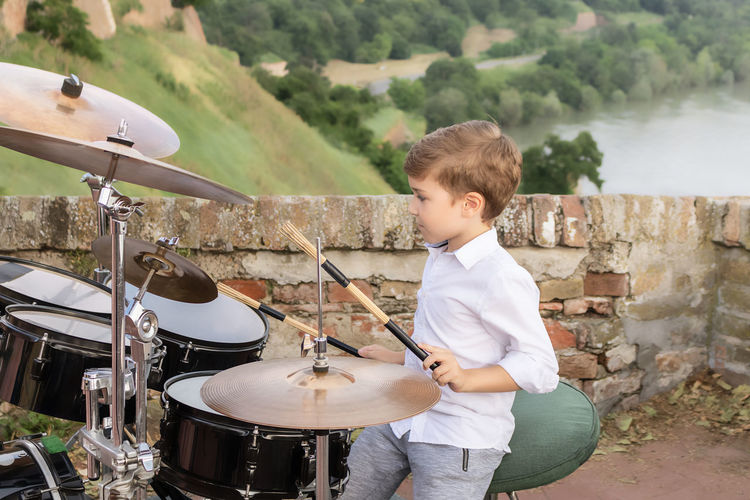 Little boy playing drums outdoors.