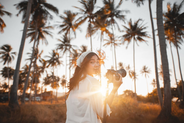 Woman with camera standing against tree during sunset