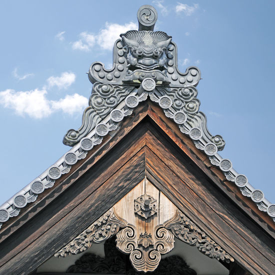Low angle view of sculptures on building against sky