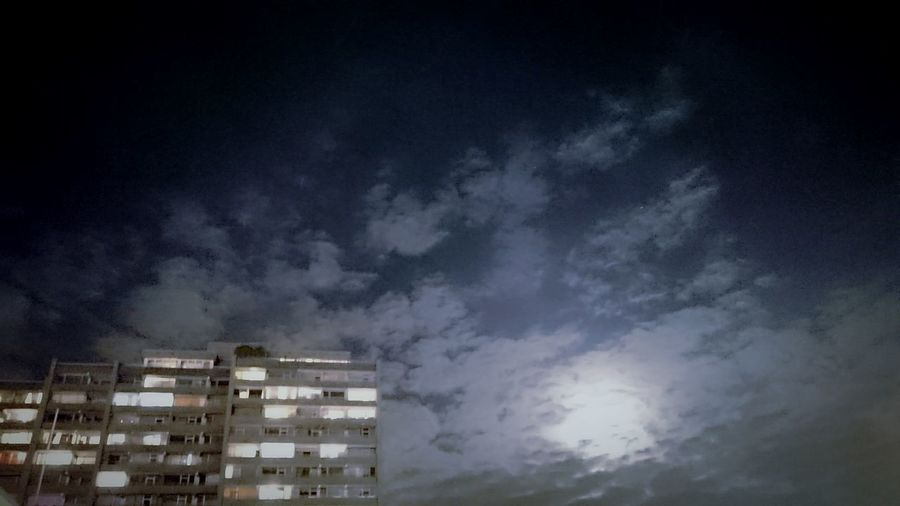 Low angle view of cityscape against sky at night