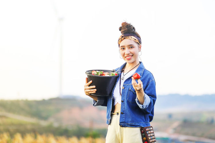 Portrait of smiling young woman holding strawberries against sky