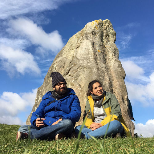Couple sitting on grassy field against sky at avebury stone circle
