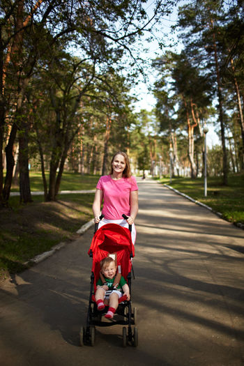 Portrait Of Happy Mother Pushing Son In Carriage Amidst Trees On Footpath At Park