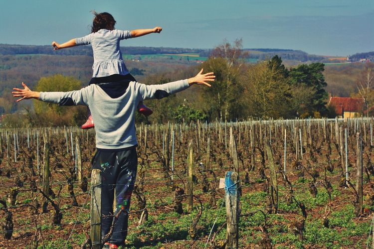 Rear view of father with daughter standing in vineyard