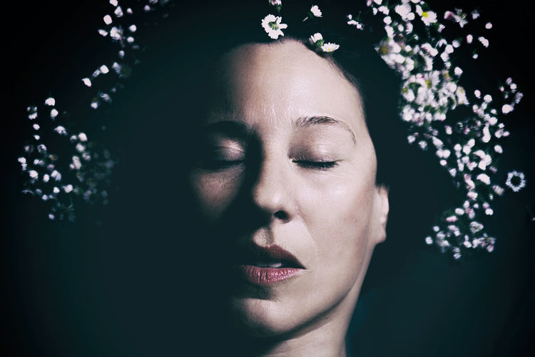 Close-up of woman with closed eyes against black background