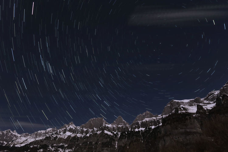 Low angle view of mountains against star trails at night