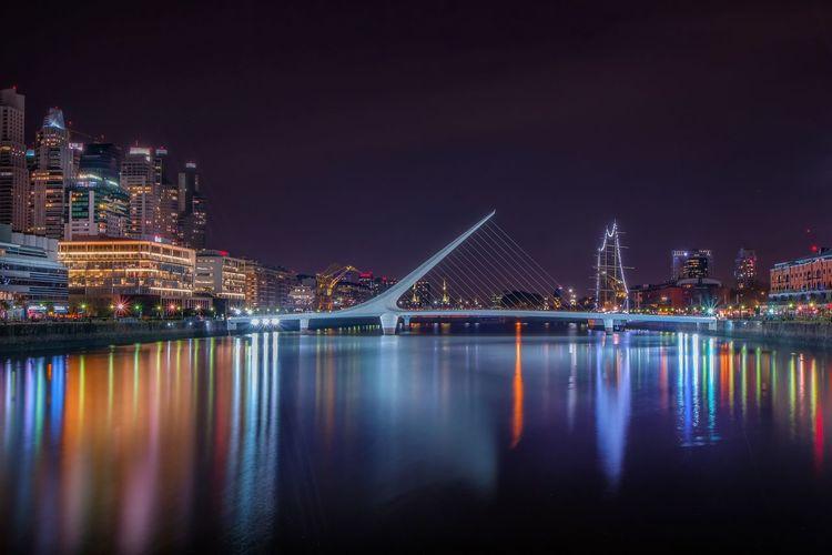 Puente de la mujer over river in city at night