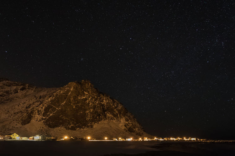 Scenic View Of Mountain Against Star Field At Night During Winter
