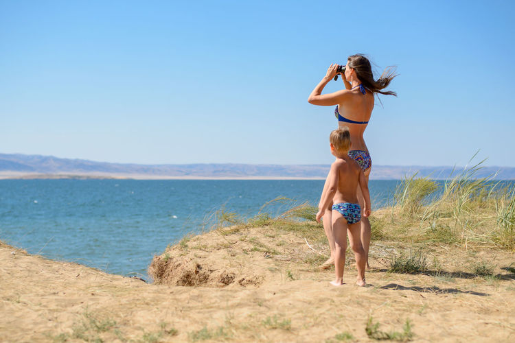 a woman with a child looking through binoculars Beach Photography Family Travel Vacations Adventure Amazing Beach Beauty In Nature Child Day Enjoying Life Full Length Land Leisure Activity Lifestyles Nature Outdoors Real People Sea Sky Summer Water Women Young Adult Young Women