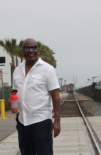 Portrait of man holding cocktail shaker while standing on railroad track