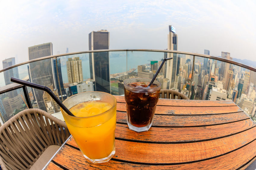 Hong Kong, China - January 1, 2016: aerial view of city skyline and cocktail from the top of The Hennessy in Wan Chai, a modern skybar in the city. HongKong Hong Kong City Hong Kong Sunset Skyline Night Cityscape Business Aerial View Light Show Laser Show Skyscraper Victoria Harbor Panorama Drink Refreshment Food And Drink Glass Drinking Straw Drinking Glass Straw Architecture Household Equipment Table Food Freshness No People Sky Built Structure Day Still Life Healthy Eating Close-up City Outdoors